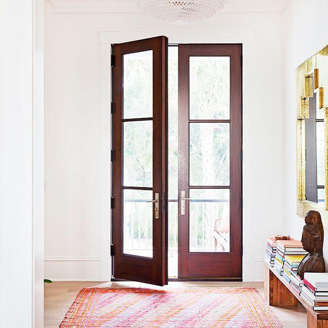 La habitación con luz natural en la casa de Rucker cuenta con puertas de piso a techo y una gran alfombra rosa y naranja