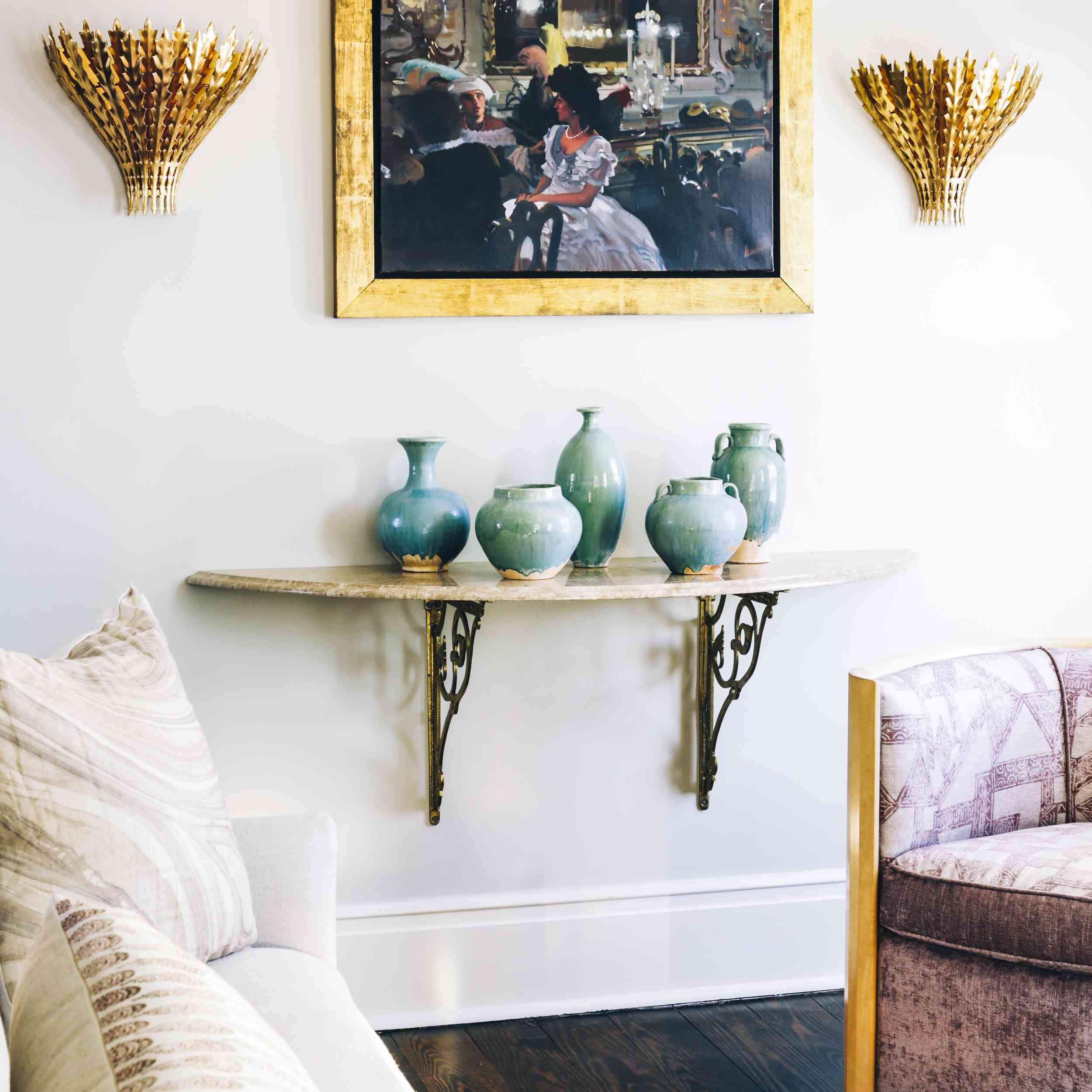 Sitting room wall with vintage art flanked by gold sconces
