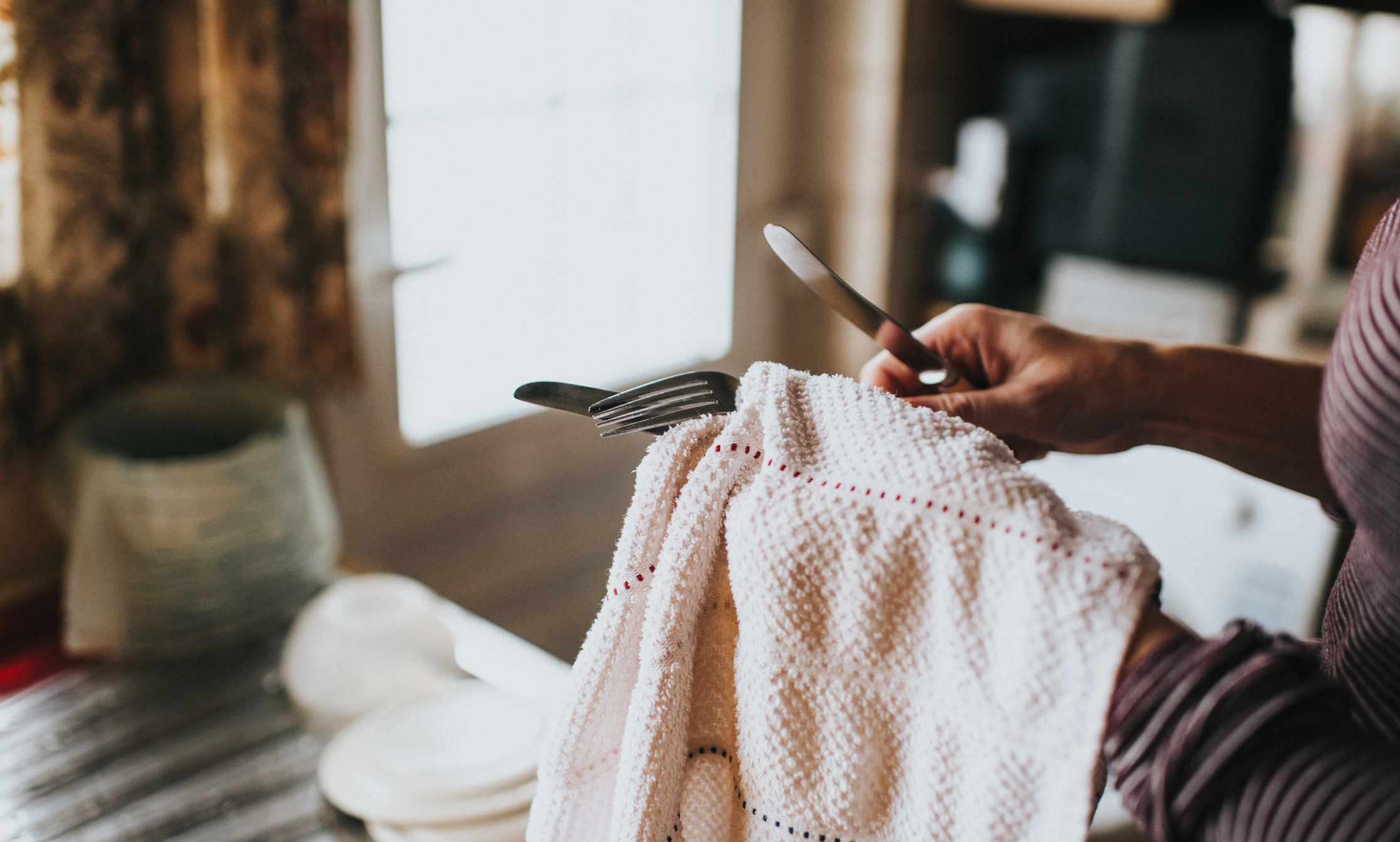 person drying off silverware with towel
