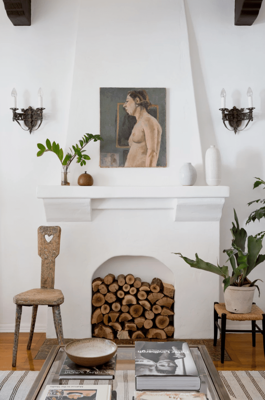 A nonfunctional fireplace that's been filled with stacked firewood logs