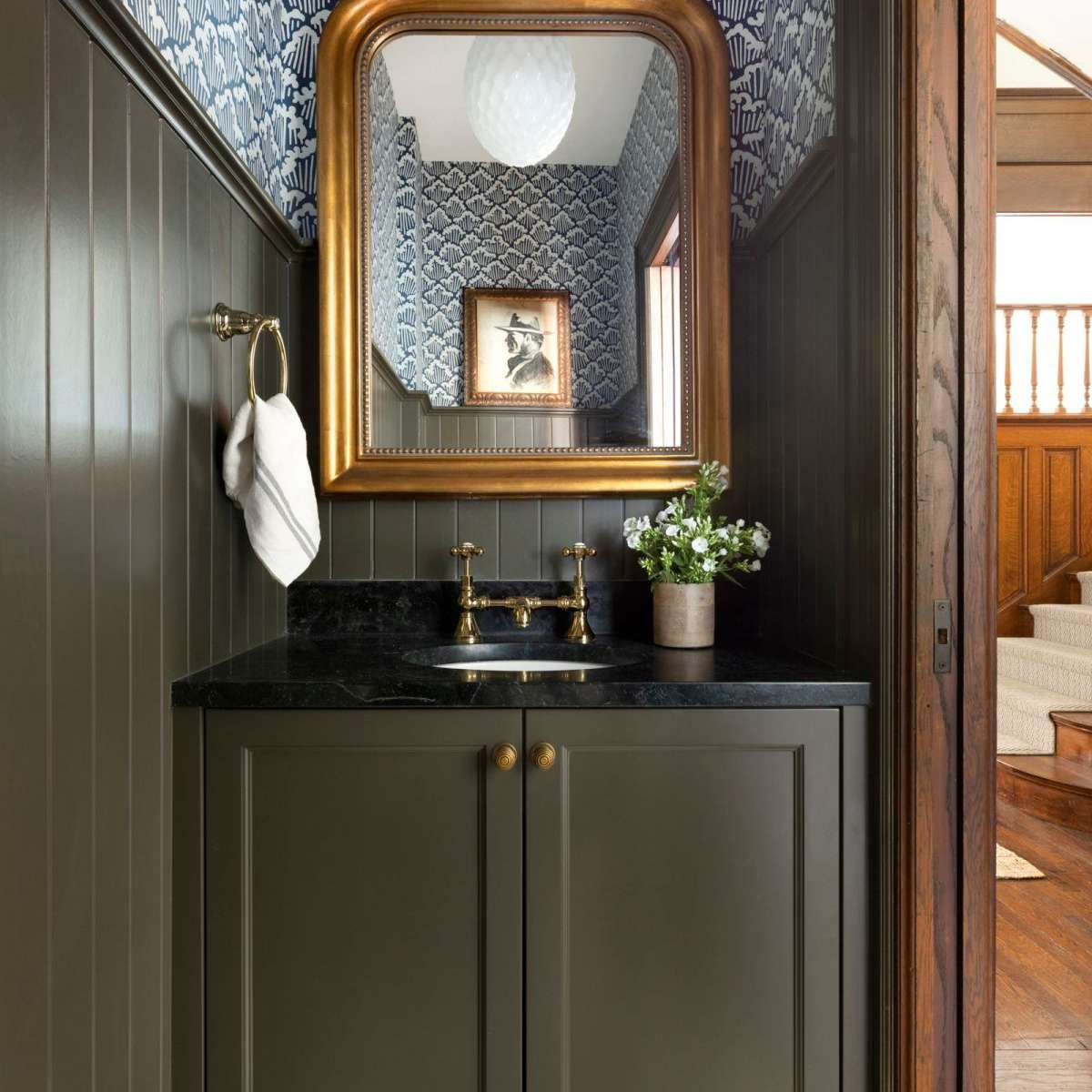Moody powder room with green cabinet and beadboard.