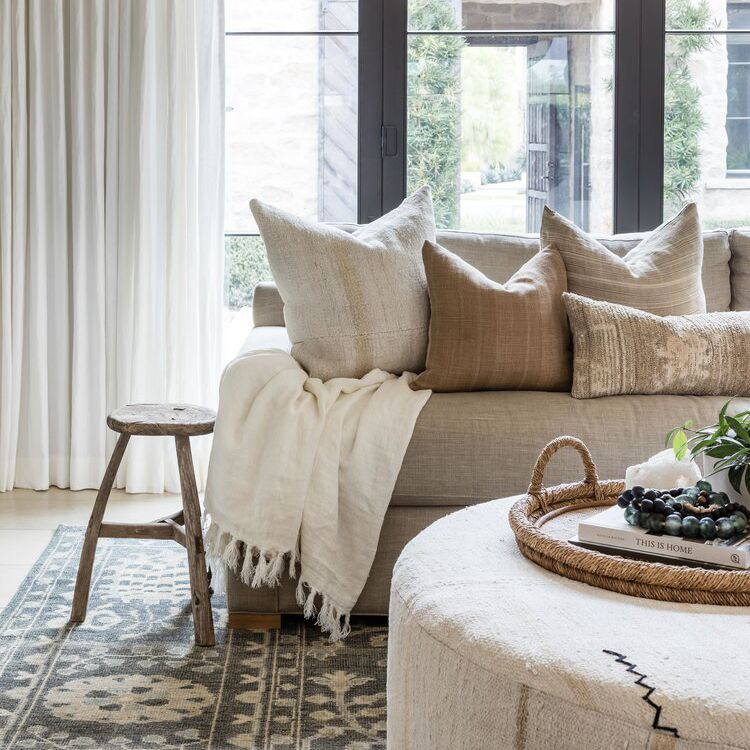 Wood stool next to a modern sofa and ottoman
