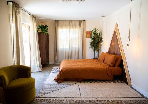 Bedroom with triangular headboard.