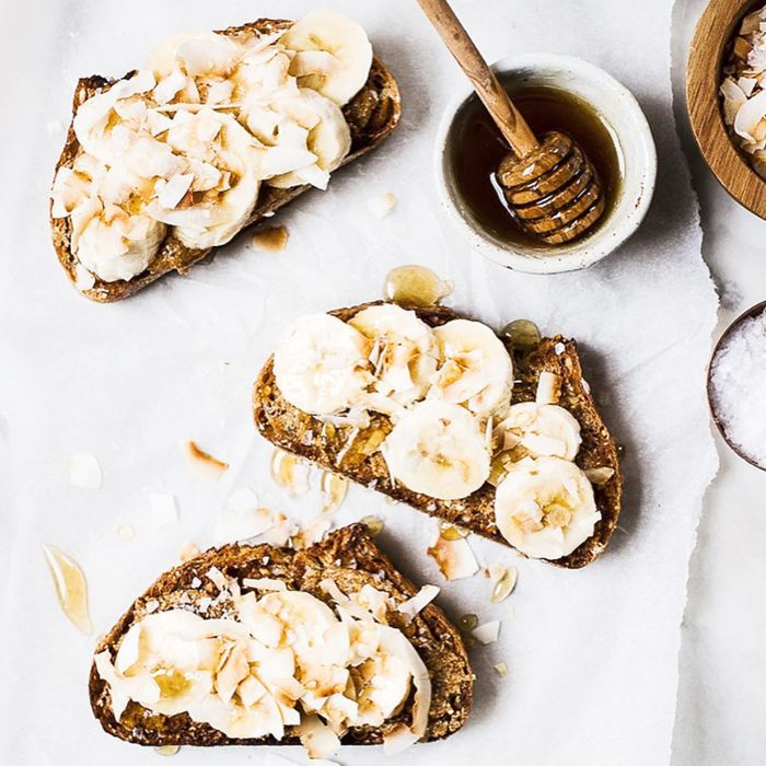 Slices of banana on toasts with a side of honey