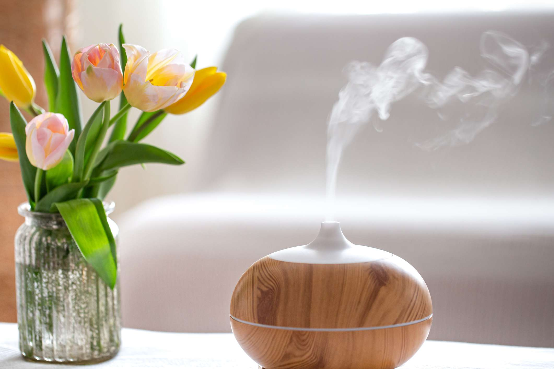 An electric diffuser on a table next to a vase filled with fresh flowers.