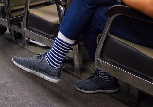 man's feet with striped socks on a train