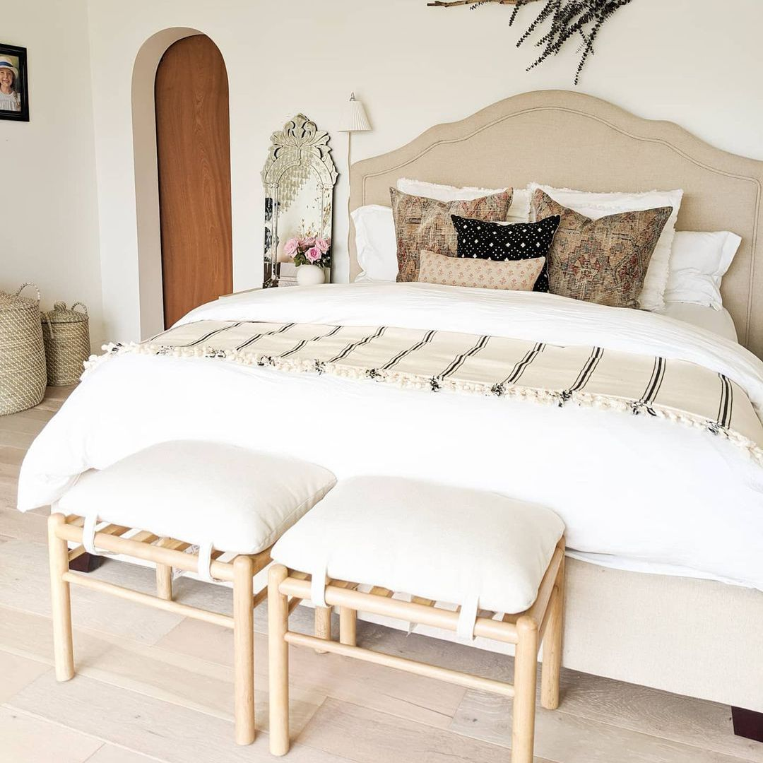 Neutral bed with white comforter.