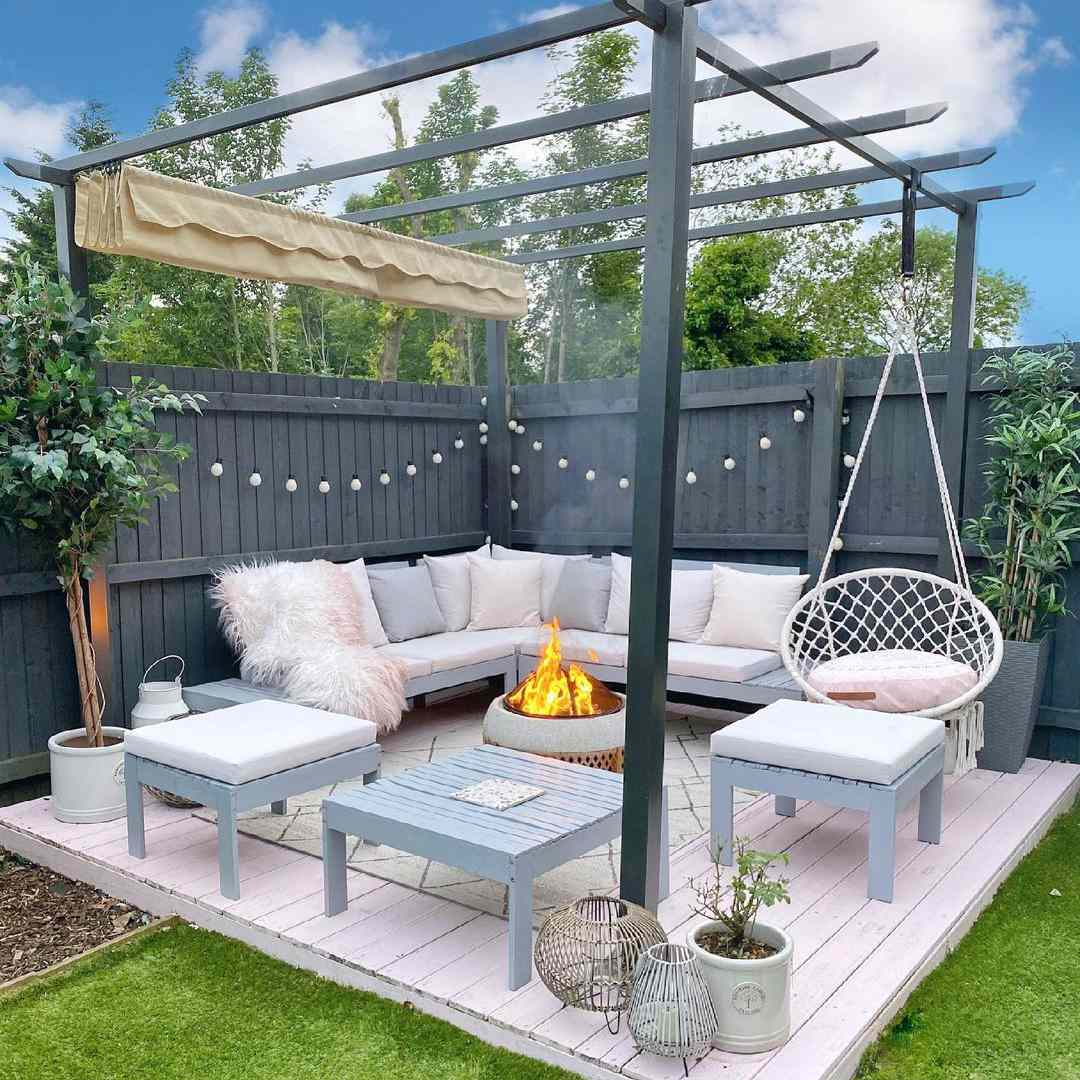 Beautiful outdoor patio with blue outdoor couch and hanging chair.