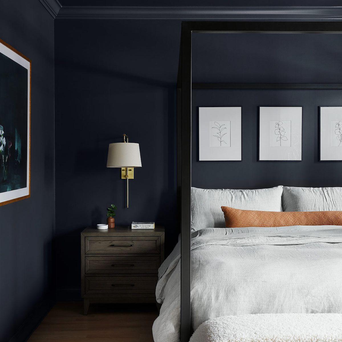 A bedroom with dark navy walls