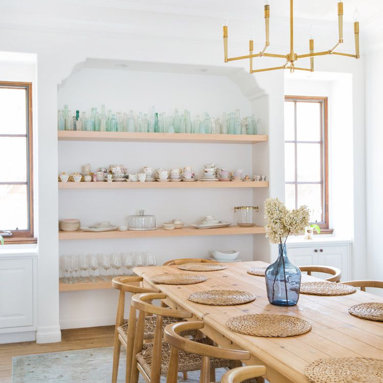 Airy dining room with open shelving alcove displaying teal and pink dishware