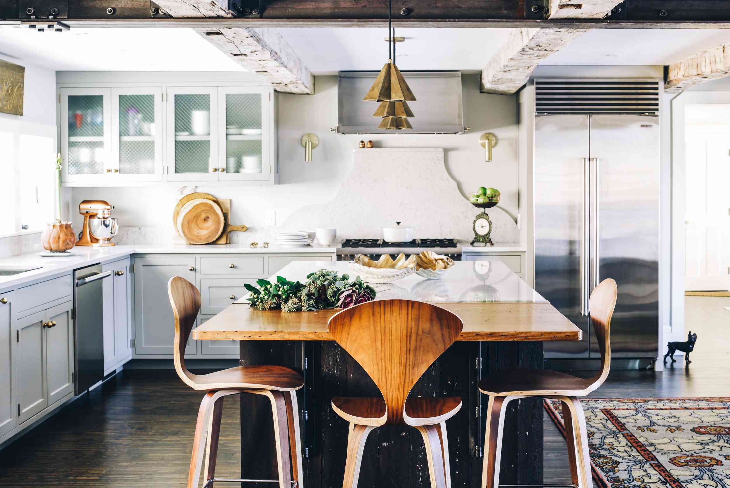 A kitchen with a bar lined with wooden seats