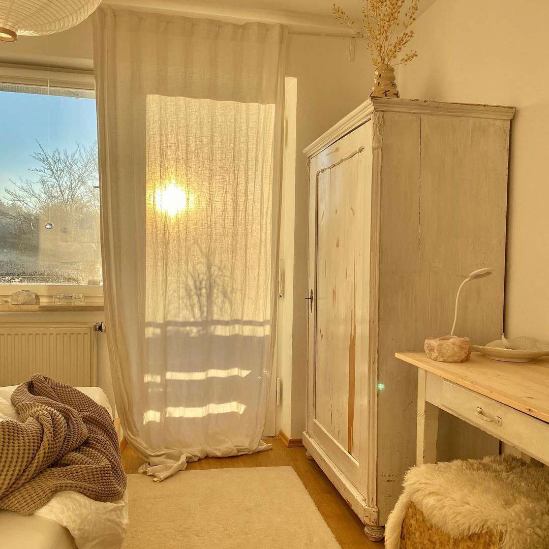 Bedroom with sun coming in through curtains.