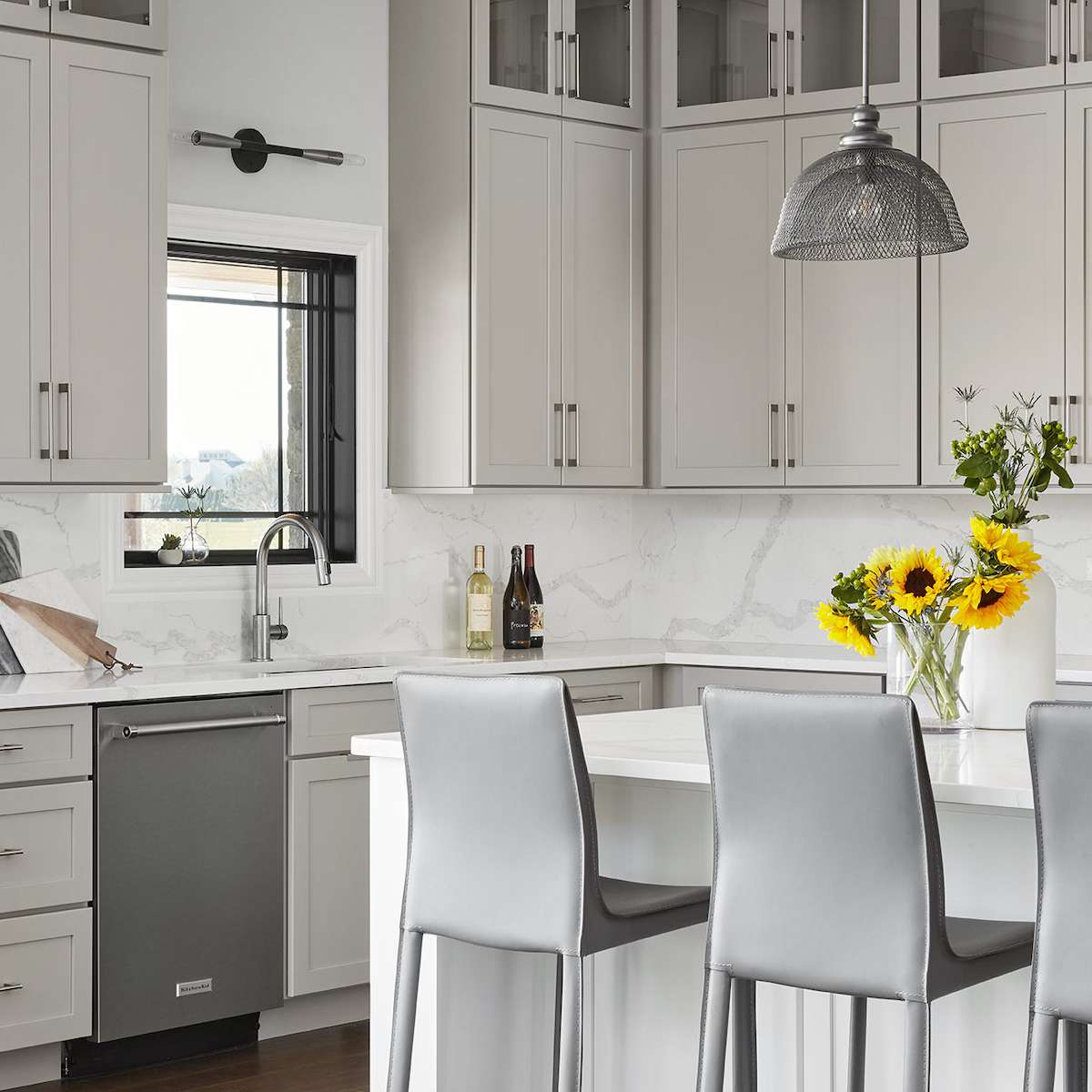 A kitchen with gray kitchen cabinets, gray barstools, and silver appliances