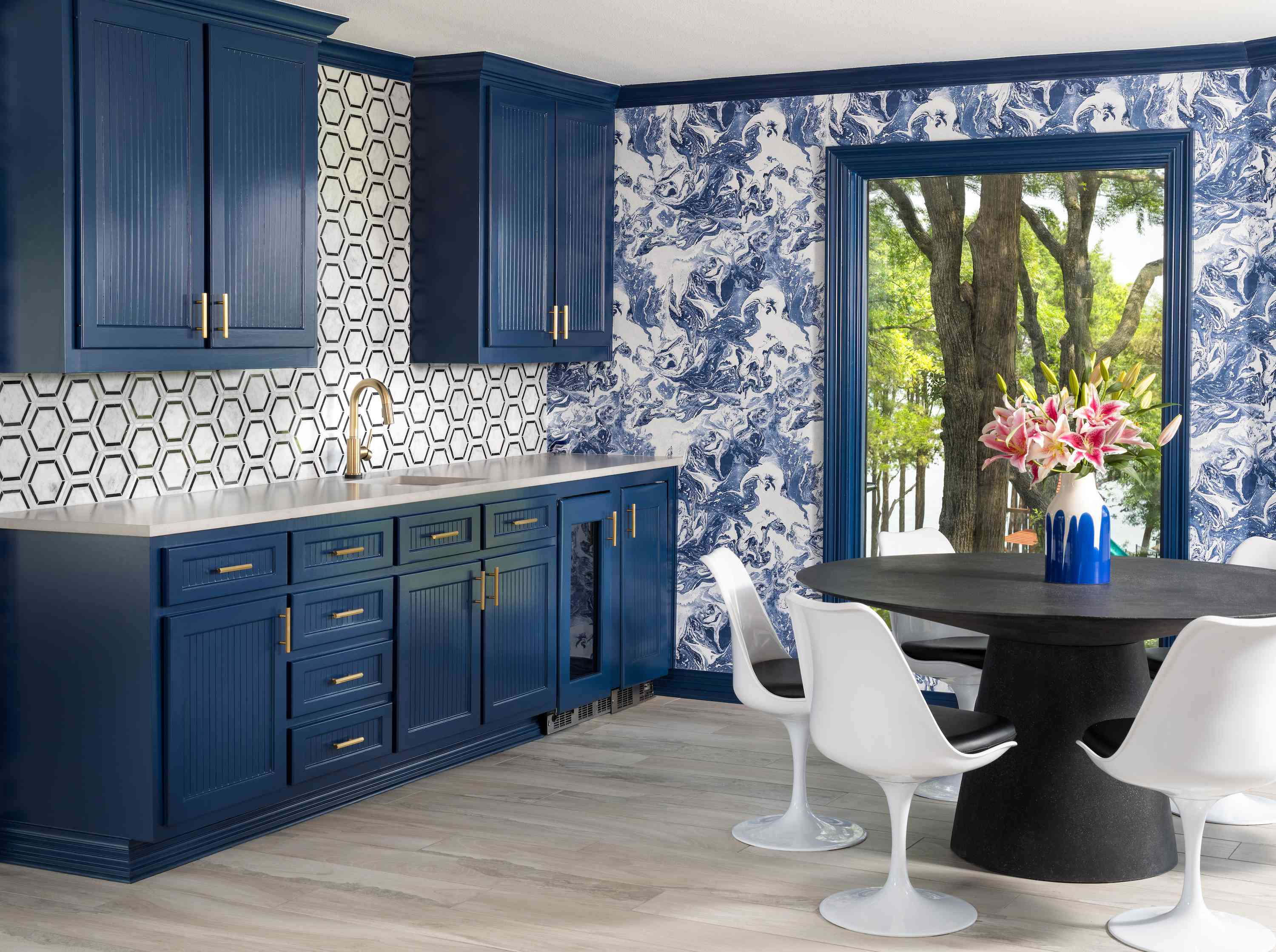 Kitchen and dining with blue patterened wallpaper.