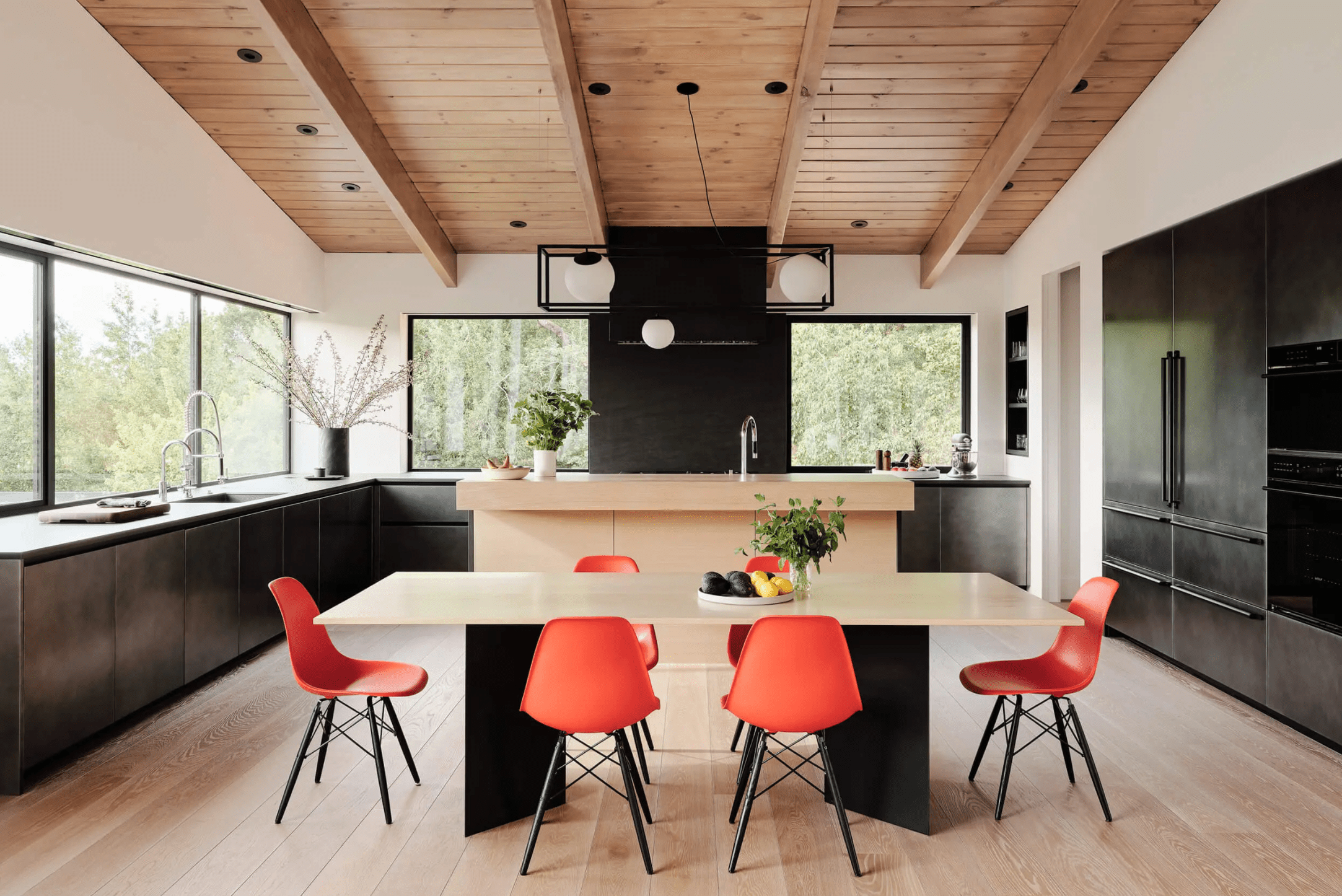 A modern kitchen with walls lined with windows—one of which acts as a sink backsplash