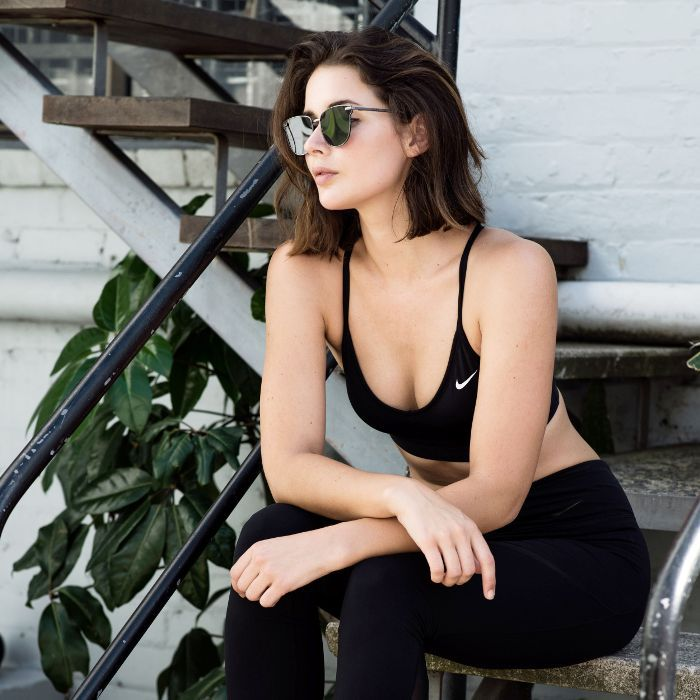 a woman in a workout outfit sitting on steps