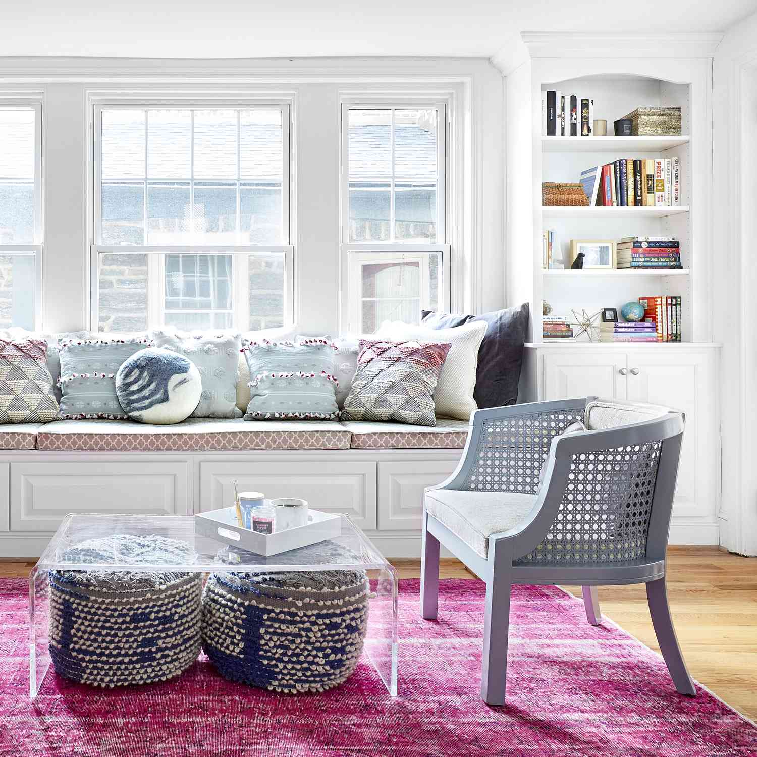Living room features clear coffee table, pink area rug