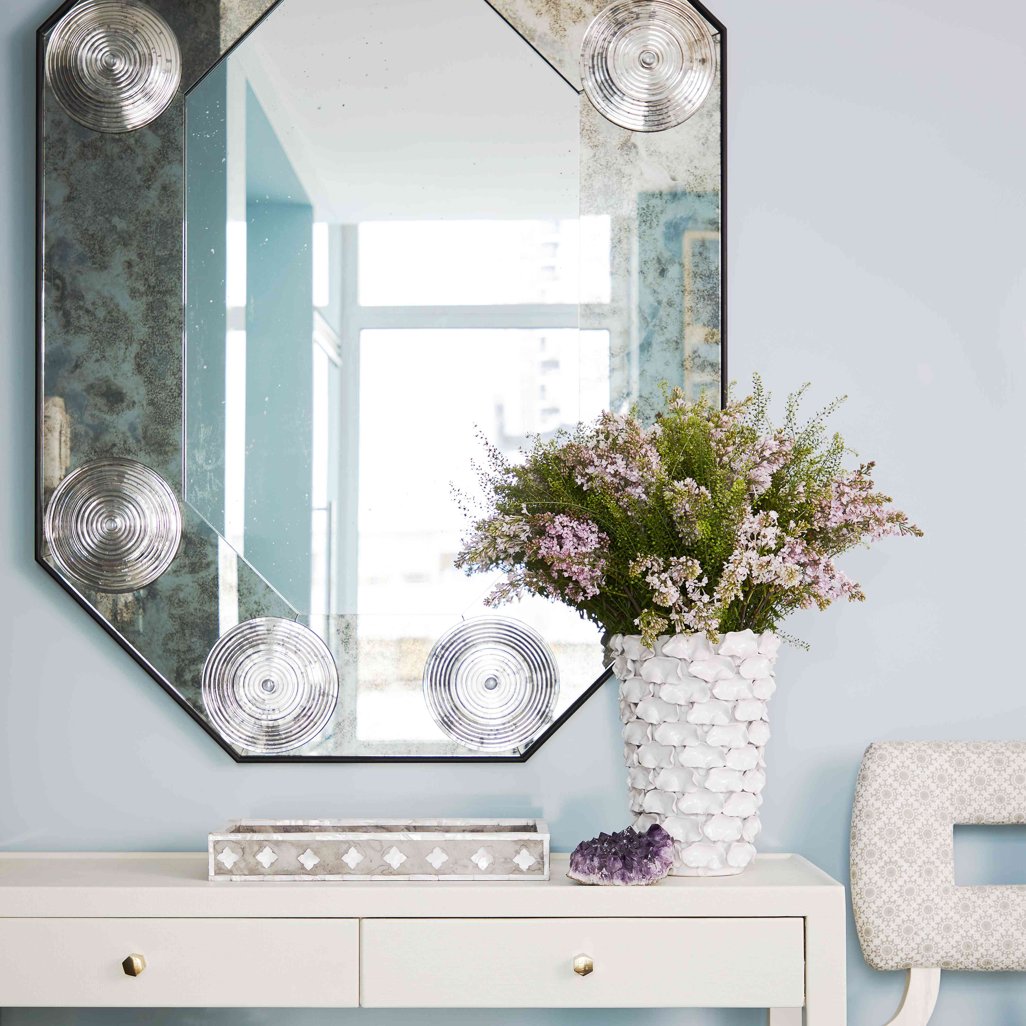 Large mirror on top of white console table.