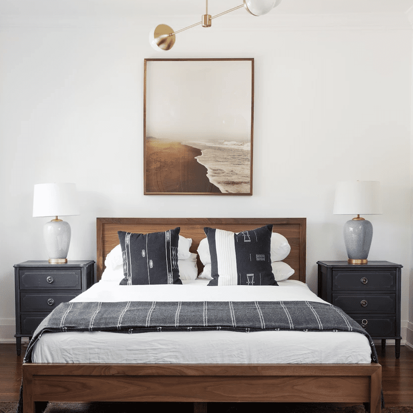 A bedroom with a geometric chandelier and two ceramic table lamps