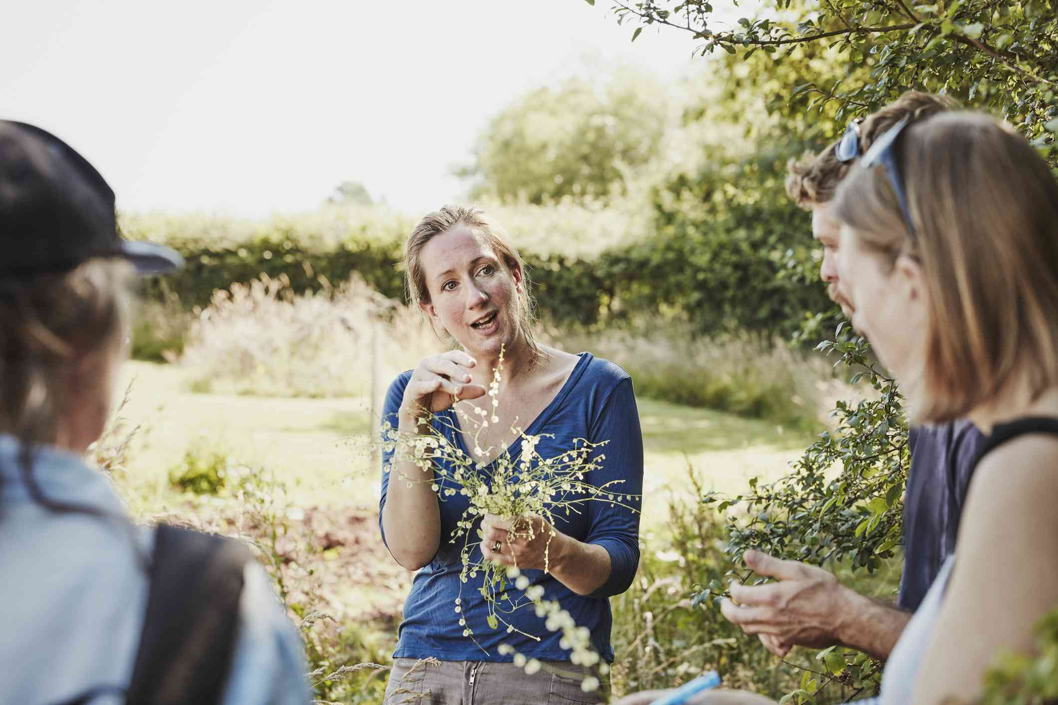 Woman holds fresh plants, talks to group about safe edible plants