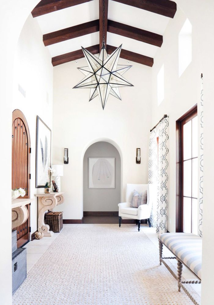 High, wood-beamed ceilings and a starburst chandelier in an entryway