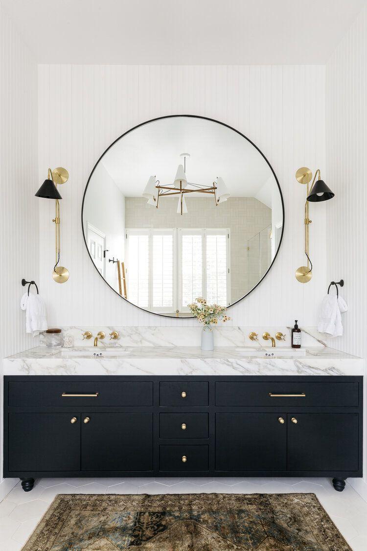 Modern bathroom with round vanity mirror, vintage area rug