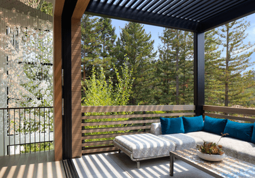 A spacious balcony with a couch and a wood-lined overhang
