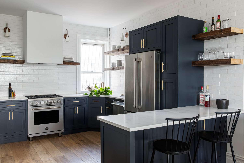Modern blue kitchen with white tile backsplash.