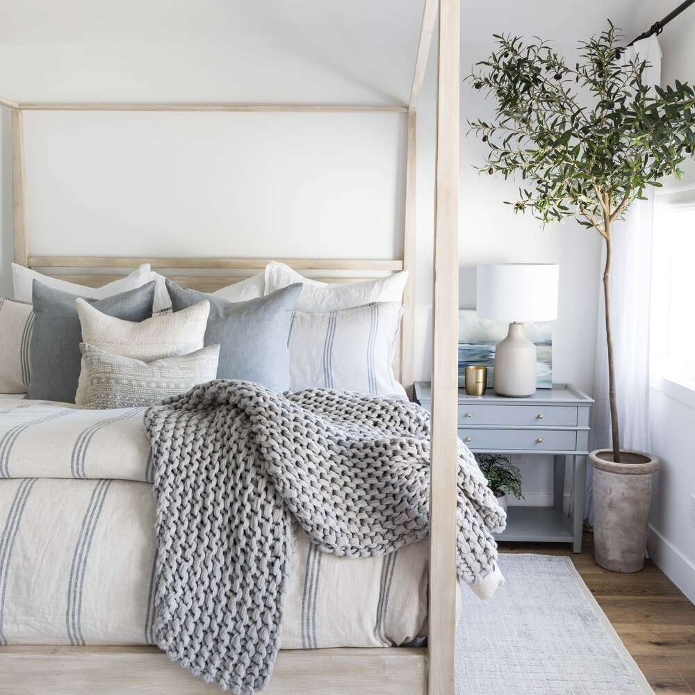 A muted bedroom with a beige canopy bed and many light blue linens