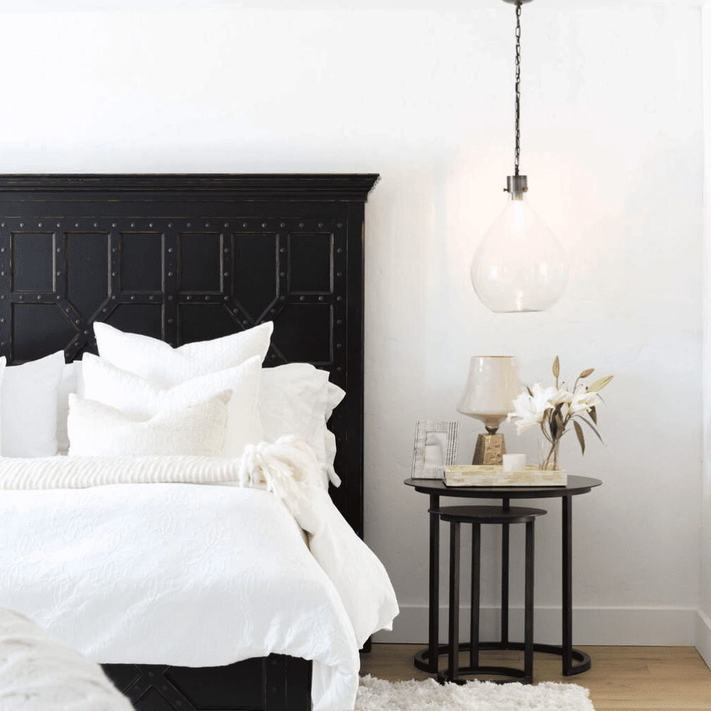 A black-and-white bedroom with two nesting nighstands