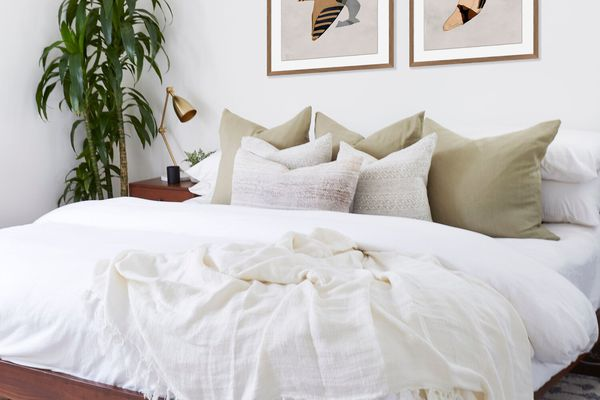 A bedroom with olive green and washed-out lavender pillows