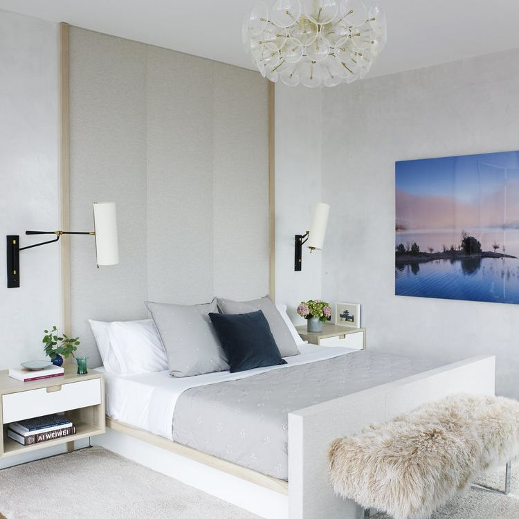 A bedroom with a floor-to-ceiling headboard.