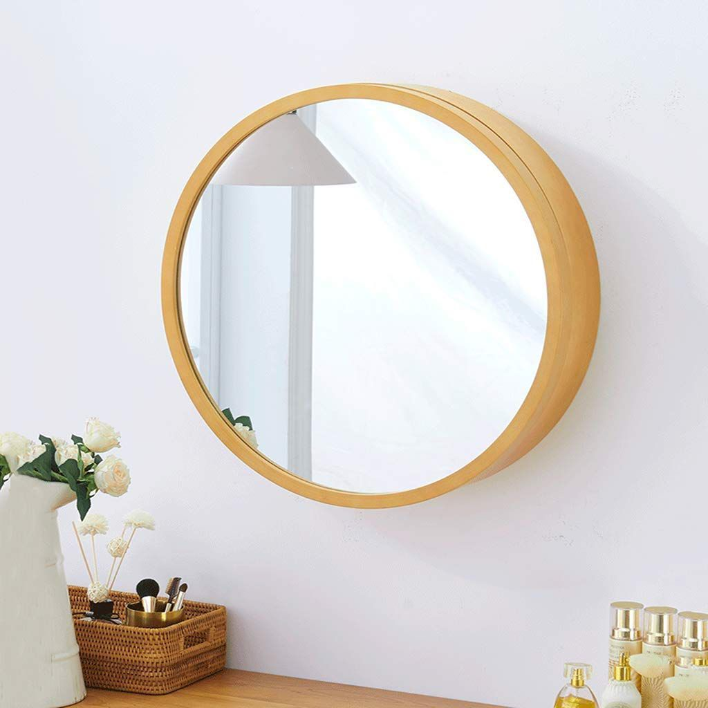 A round, wooden, mirrored medicine cabinet hung on a white wall.