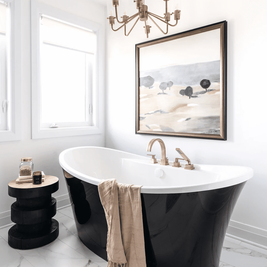 A bathroom with a large black freestanding tub and marble floors