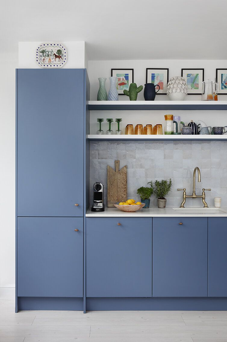A kitchen with blue cabinets and iridescent light gray tiles
