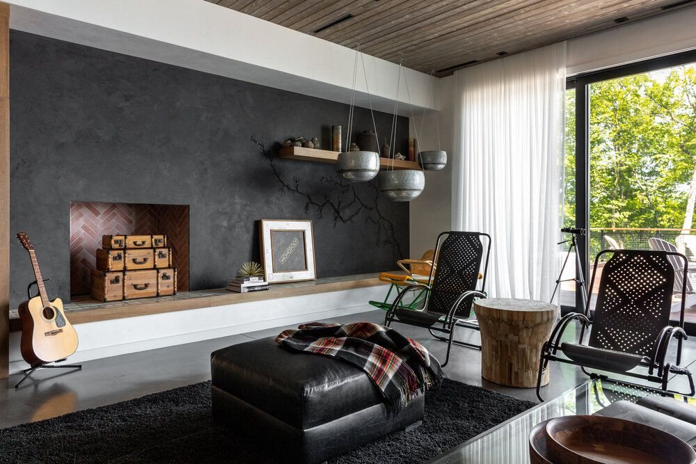 An industrial living room with black walls and furniture