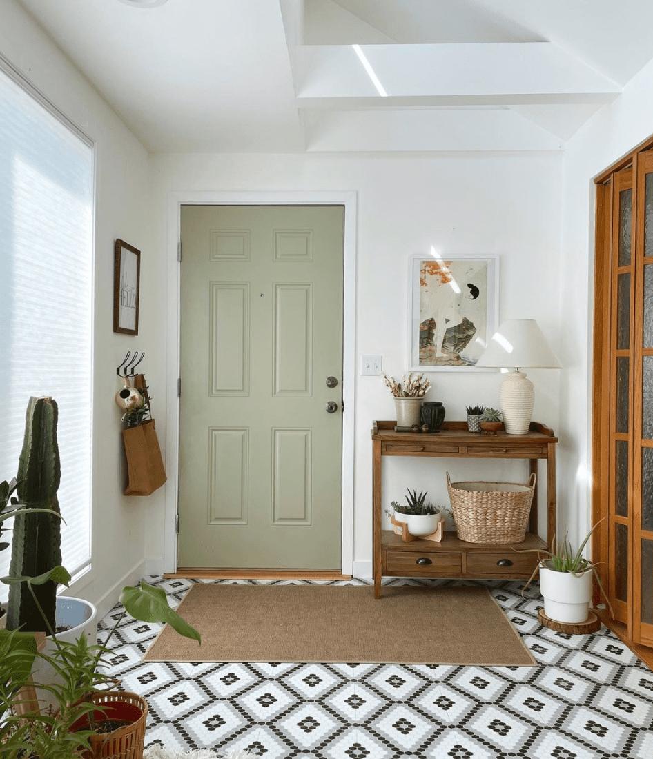 Sage green door next to natural wood decor.