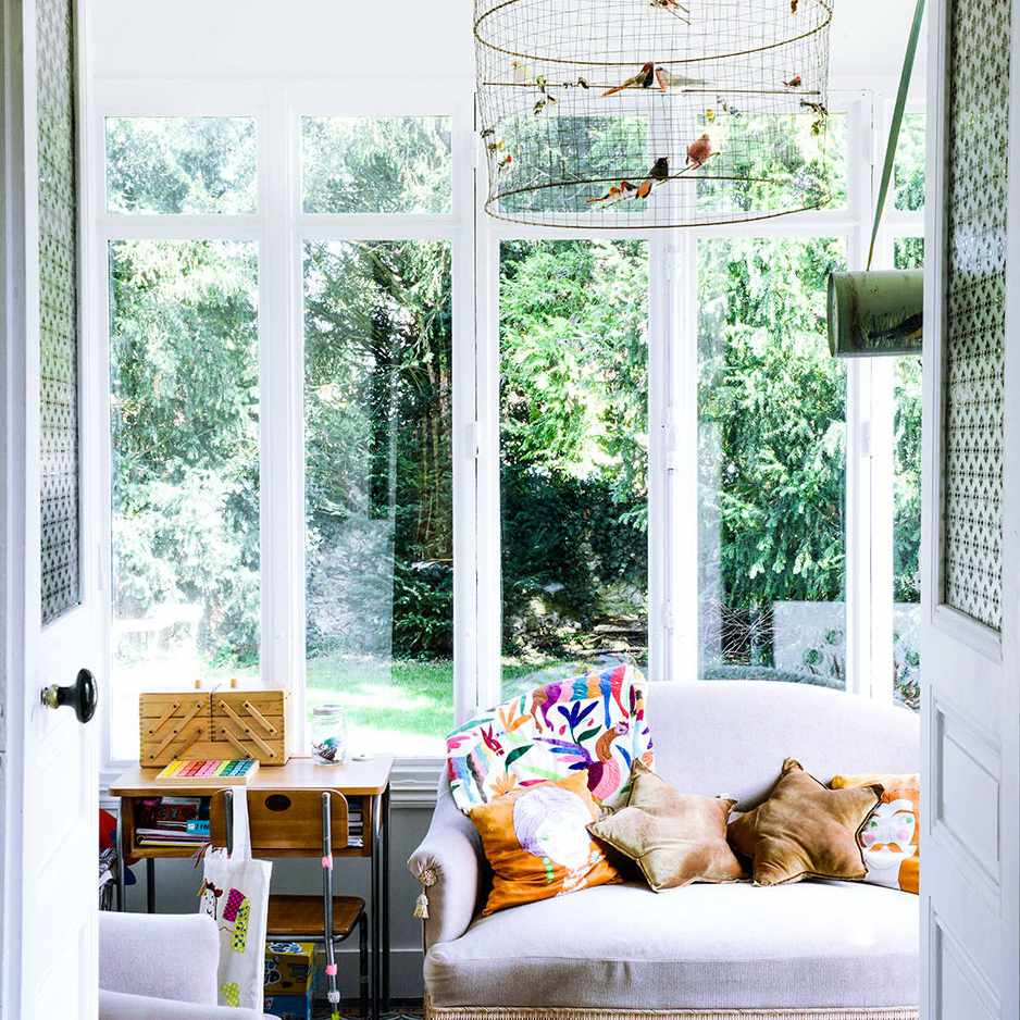 Whimsical family room with bird cage light and pink furniture