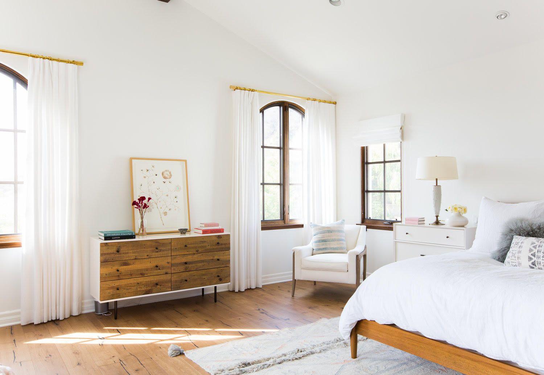 White window treatments in neutral bedroom.