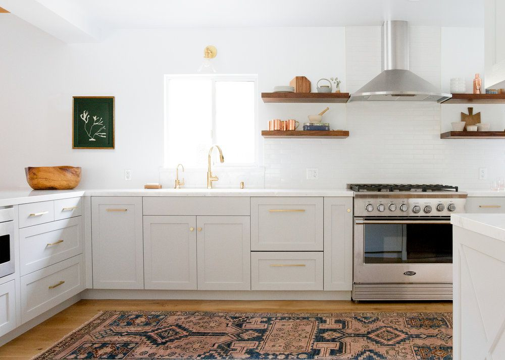 Kitchen with pale gray cabinets and gold hardware