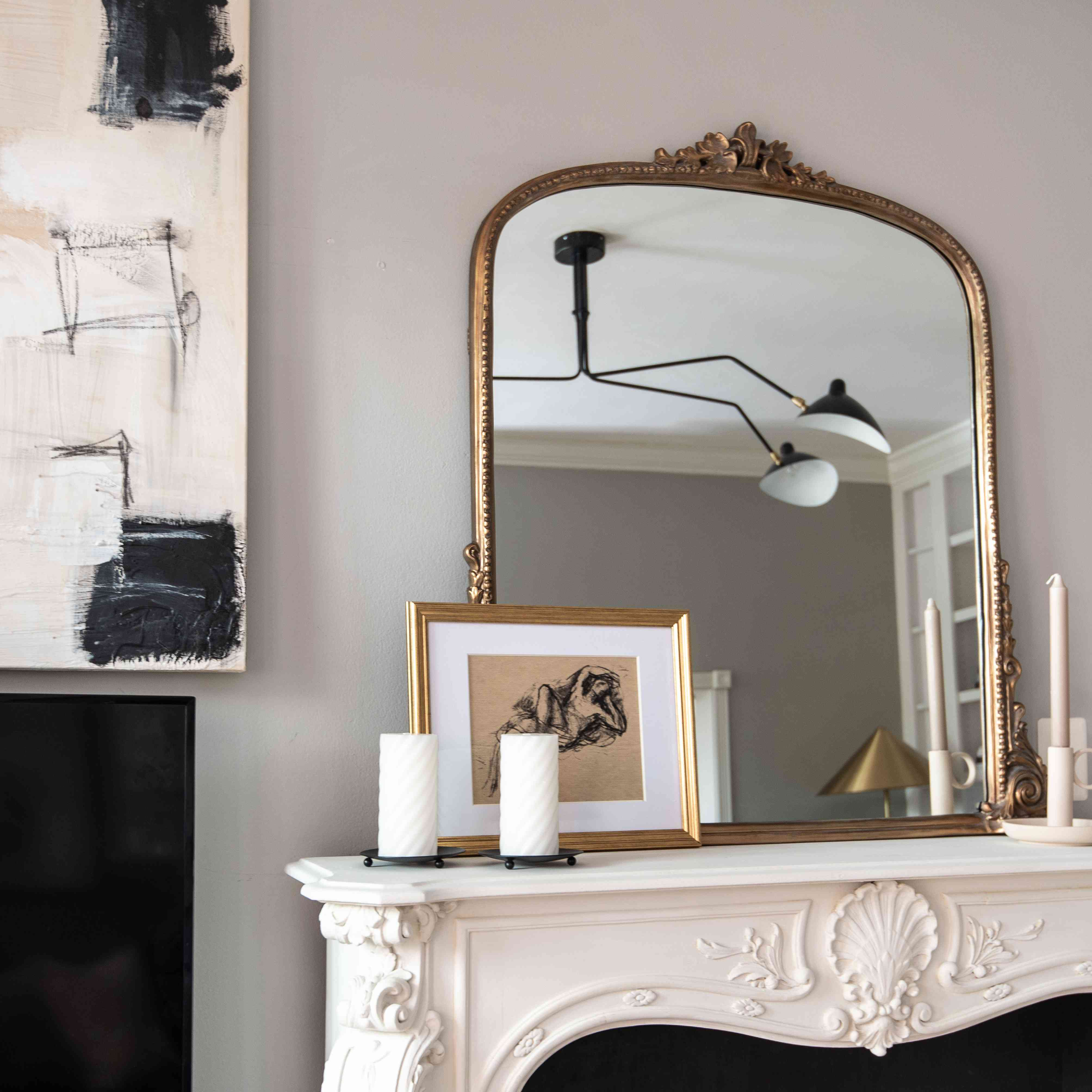 Gold mirror and other gold accessories on mantle.