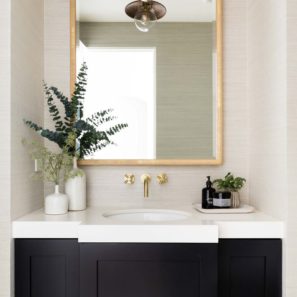 A bathroom lined with beige textured wallpaper