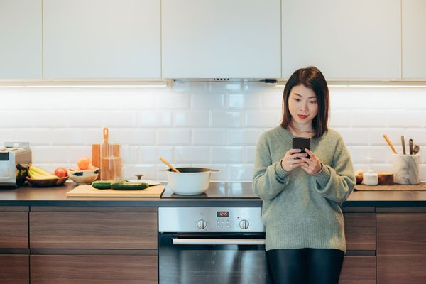 Young woman leans agains kitchen counter, uses smartphone