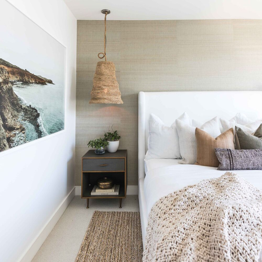 Coastal bedroom with rug layered over carpet.