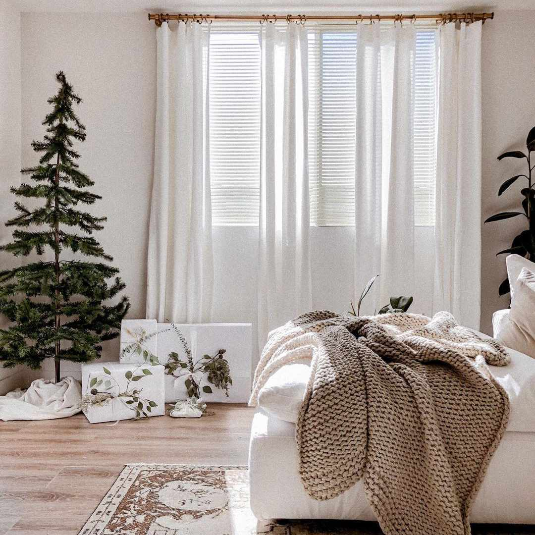 Neutral bedroom with Christmas tree.