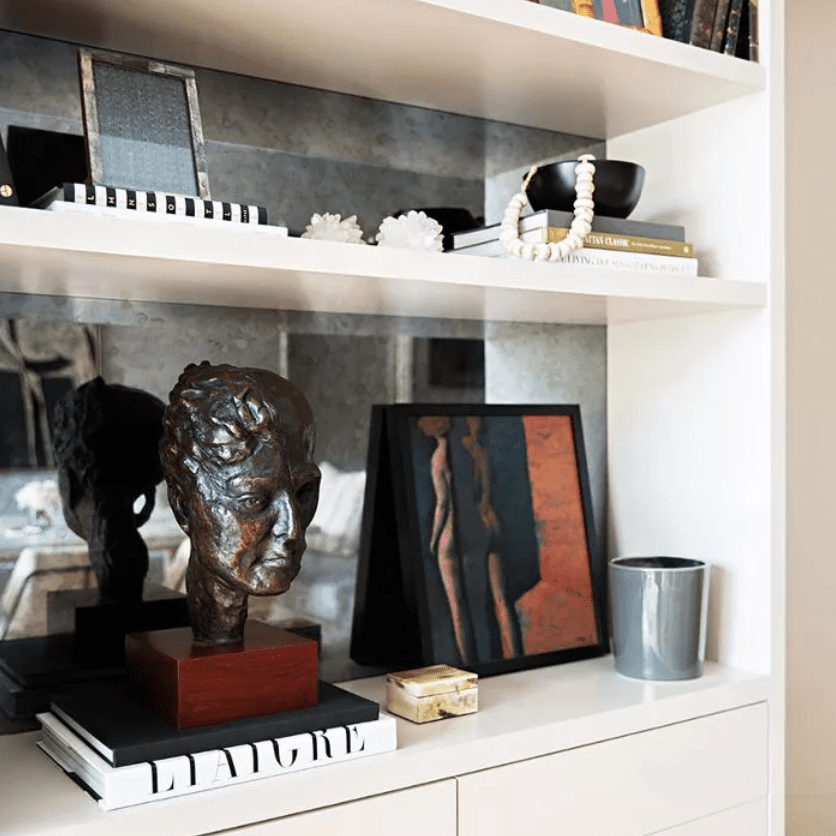Art on bookshelf, surrounded by decorative objects and books