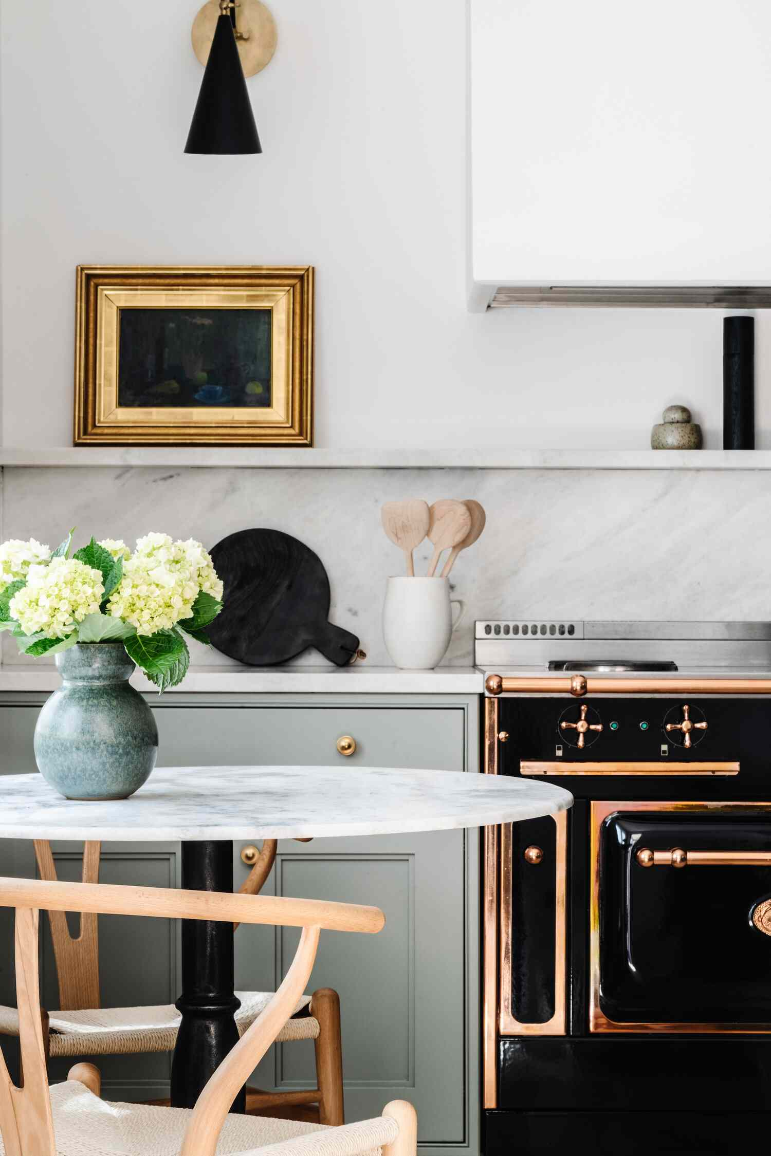 A kitchen with a marble backsplash topped with a small matching shelf