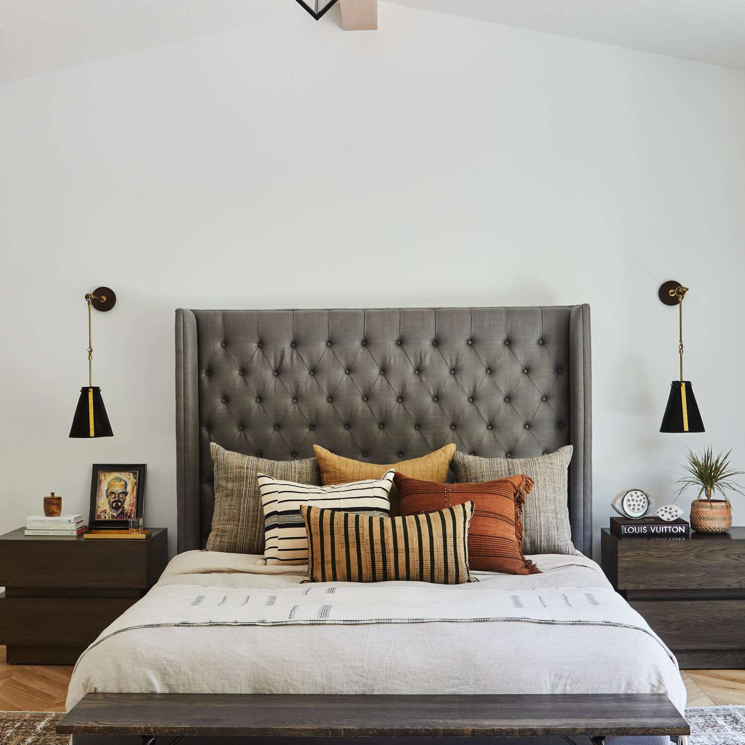 A bedroom with two black and gold sconces and a matching chandelier