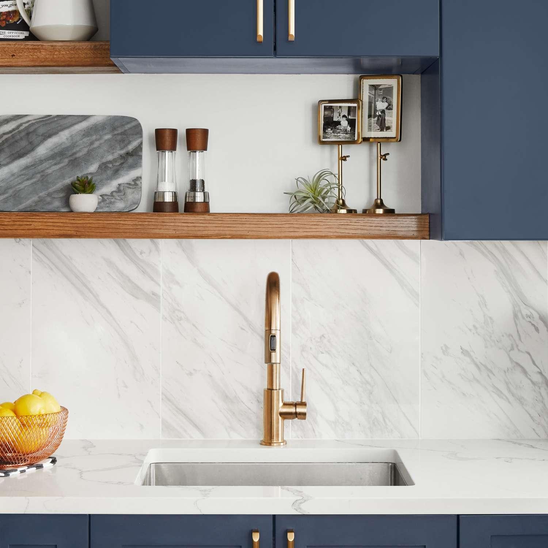 A vibrant blue kitchen with a marble backsplash