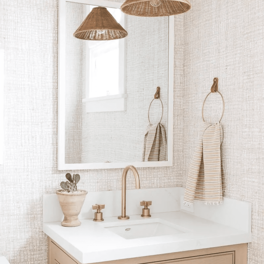 A bathroom with light pink textured wallpaper